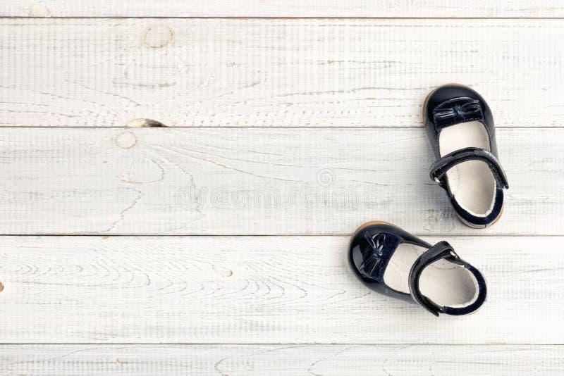 Sapatas escuramente azuis do bebê do verão no fundo de madeira foto de stock