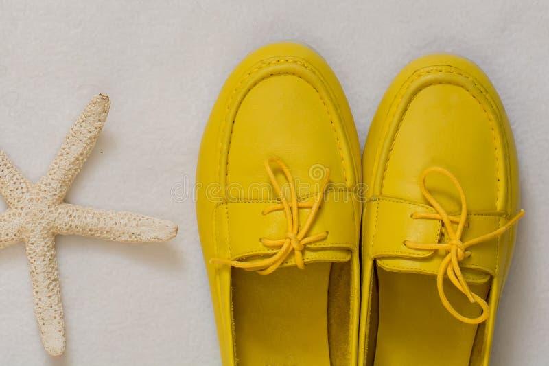 Sapatas fêmeas amarelas em um fundo branco foto de stock