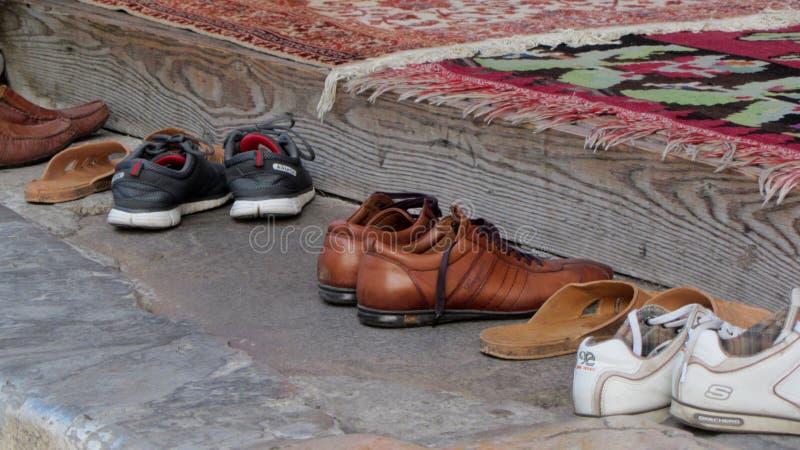 Sapatas fora da mesquita durante a oração imagens de stock royalty free