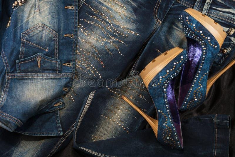 Sapatas luxuosos da sarja de Nimes das mulheres nos cristais de rocha e calças de brim nos cristais de rocha em uma seda preta Fu fotografia de stock royalty free