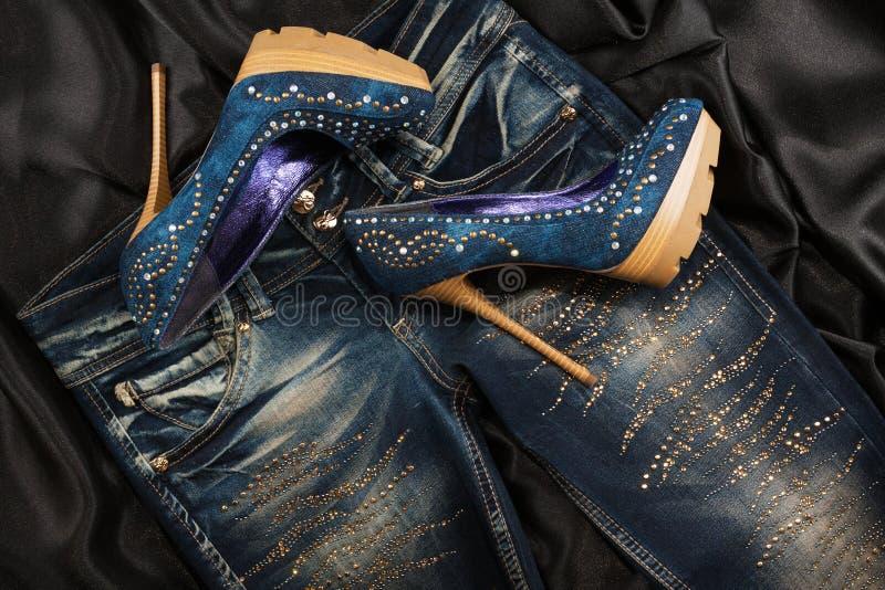 Sapatas luxuosos da sarja de Nimes das mulheres nos cristais de rocha e calças de brim nos cristais de rocha em uma seda preta Fu fotos de stock