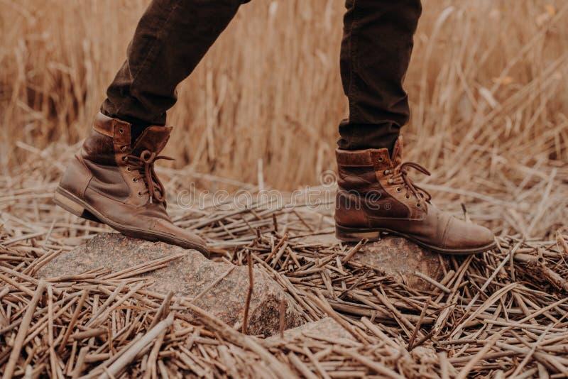 Sapatas marrons dos homens no território rural Masculino irreconhecível nos trouses e nas botas Calçados velhos de couro Caminhad fotos de stock royalty free