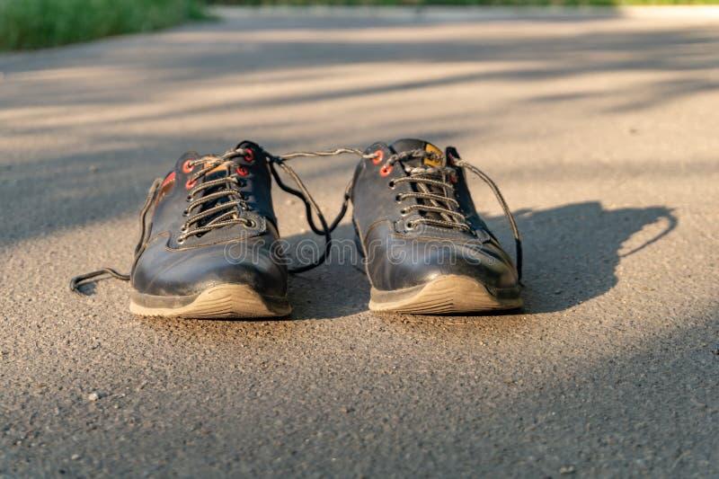 Sapatas no suporte do asfalto apenas que espera o proprietário para jogar esportes na rua fotografia de stock royalty free