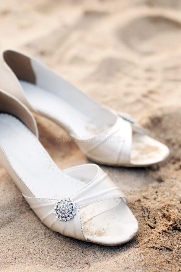 Sapatas nupciais no banquete de casamento da praia imagem de stock
