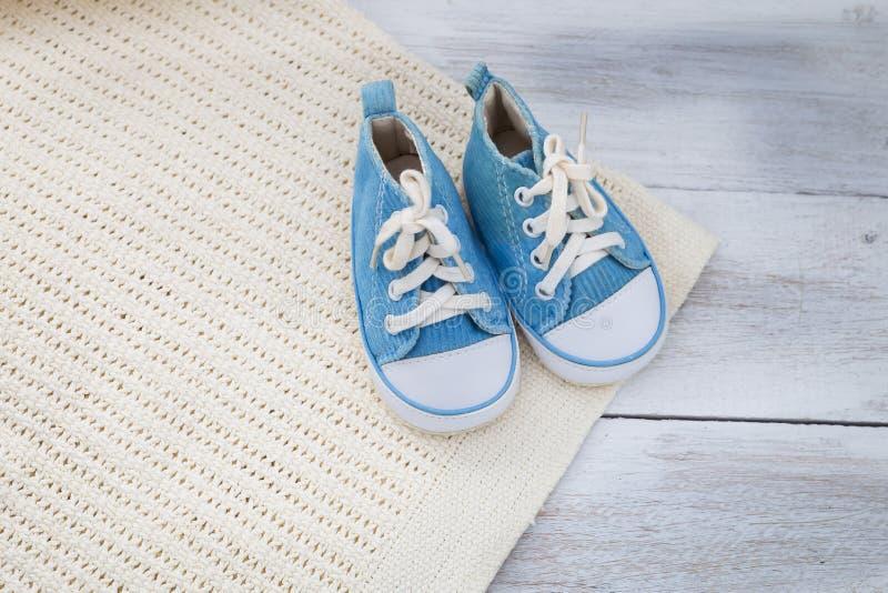 Sapatas para um bebê e uma cobertura em um fundo de madeira foto de stock