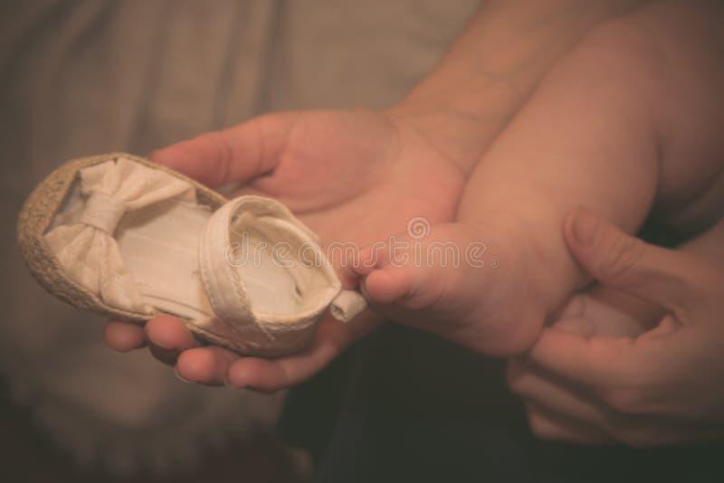 Sapatas para um beb? rec?m-nascido, montantes do beb? no fundo dos p?s pequenos A mamã tenta sobre sapatas a seu bebê recém-nasci imagens de stock royalty free