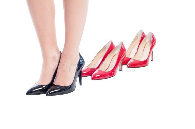 Sapatas pretas da mulher de negócio contra o vermelho do salto alto fotografia de stock