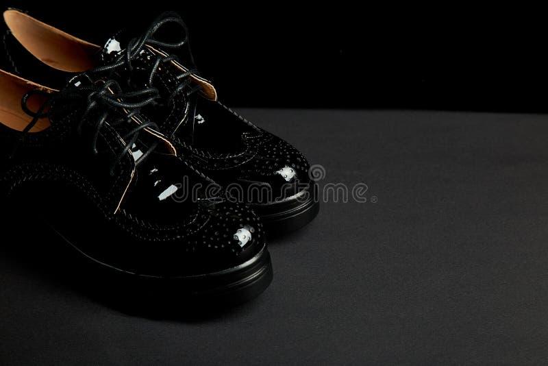 Sapatas pretas fêmeas da plataforma de oxford da mulher no fundo preto fotografia de stock royalty free