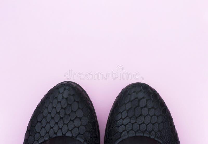 Sapatas pretas no fundo cor-de-rosa, vista superior, espaço da cópia fotos de stock royalty free