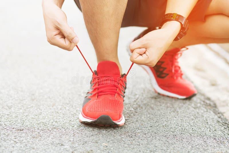 Sapatas Running Close up descal?o das sapatas running Atleta masculino que amarra la?os para movimentar-se na estrada imagens de stock