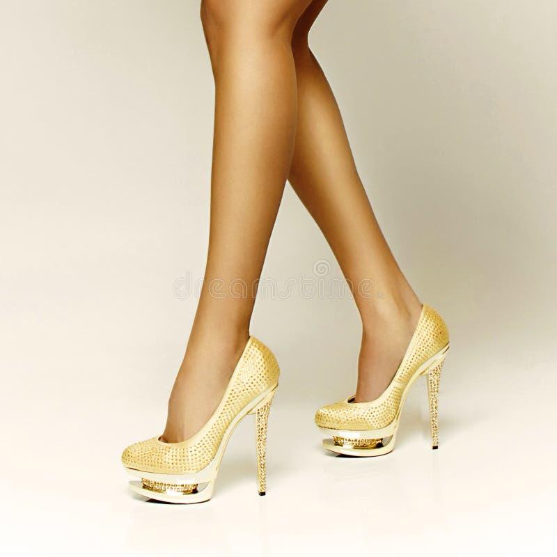 Sapatas 'sexy' da menina do ouro foto de stock royalty free