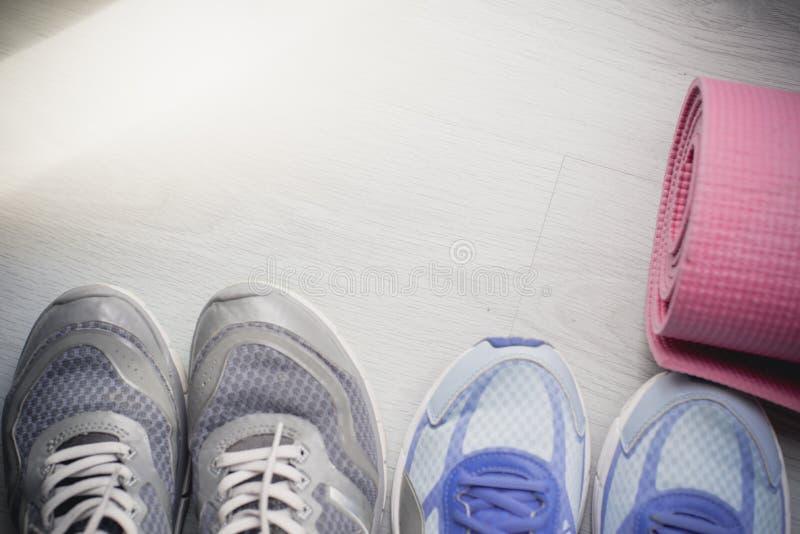 Sapatas sujas do esporte no assoalho com esteira da ioga em casa lifestyle imagens de stock royalty free