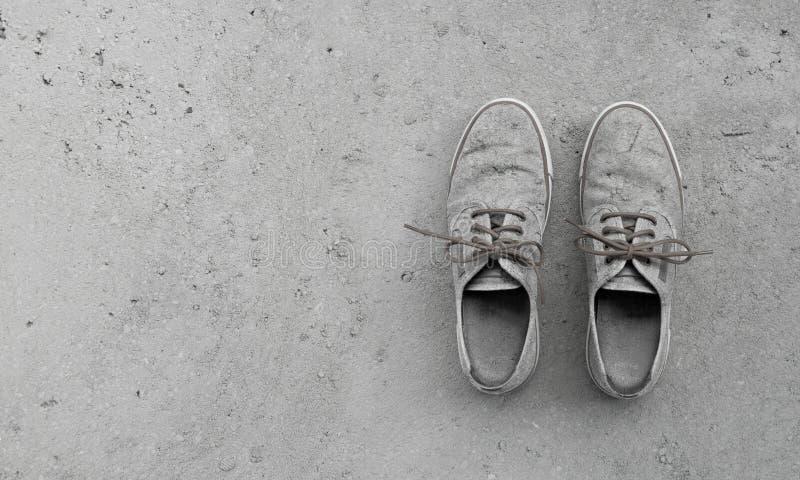 Sapatas sujas velhas da camuflagem no fundo concreto foto de stock