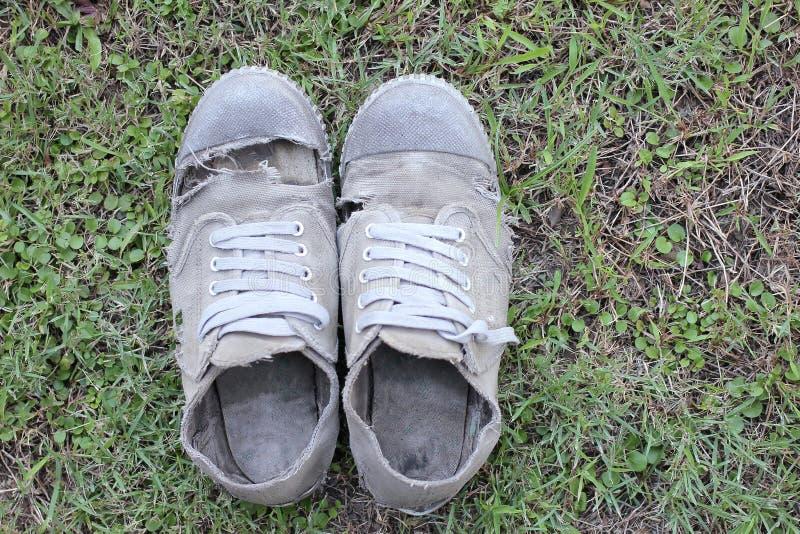 Sapatas velhas sujas no fundo da grama, ainda estilo de vida imagens de stock royalty free