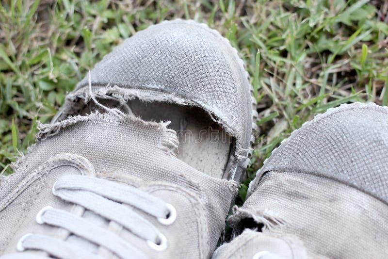 Sapatas velhas sujas no fundo da grama, ainda estilo de vida imagem de stock royalty free