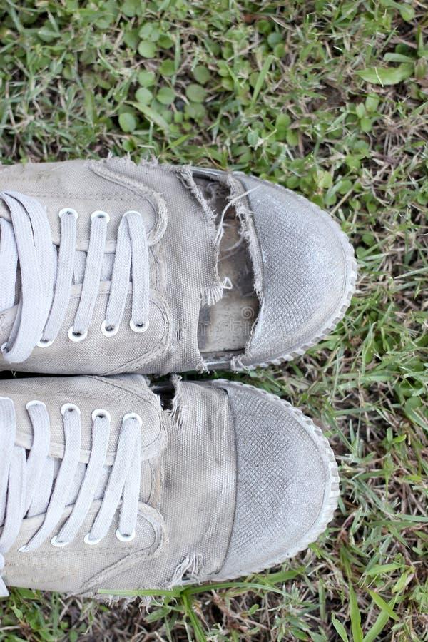 Sapatas velhas sujas no fundo da grama, ainda estilo de vida foto de stock royalty free