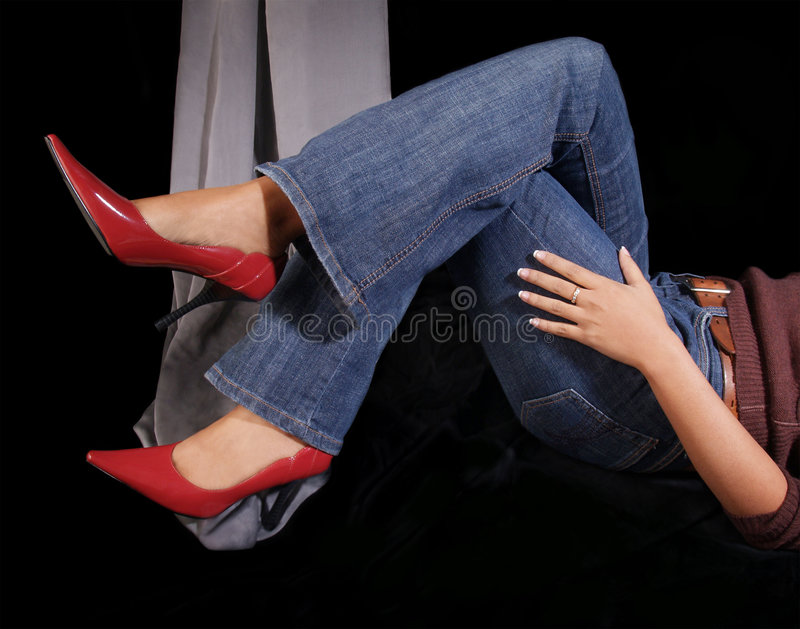Sapatas vermelhas do salto elevado com calças de brim. foto de stock royalty free