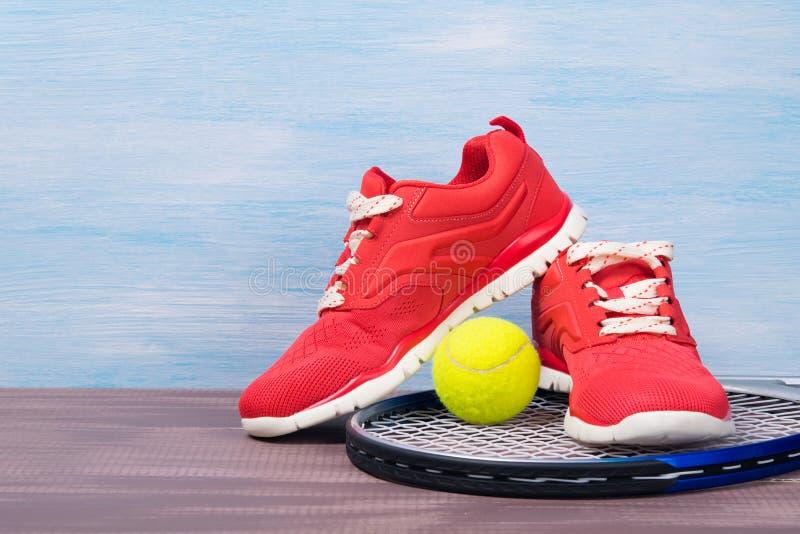 Sapatas vermelhas dos esportes em uma raquete de tênis, em um fundo azul fotografia de stock royalty free