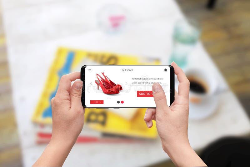 Sapatas vermelhas em linha da compra da mulher com telefone esperto imagem de stock royalty free