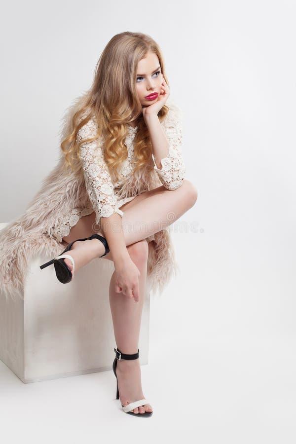Sapatas vestindo dos saltos altos da mulher loura no fundo branco, retrato da forma fotos de stock