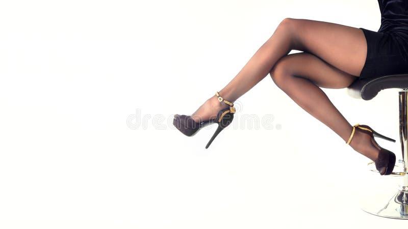 Sapatas vestindo dos saltos altos da mulher 'sexy' e saia curto que sentam-se na cadeira do escritório Isolado no branco imagens de stock