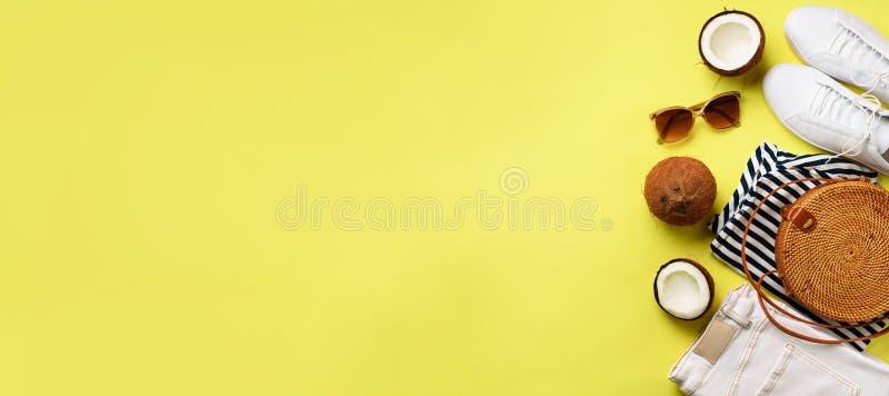 Sapatilhas brancas fêmeas, calças de brim, t-shirt listrado, saco do rattan, coco e óculos de sol no fundo amarelo com espaço da  fotografia de stock royalty free