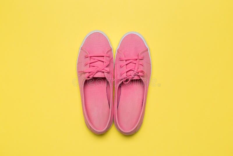 Sapatilhas cor-de-rosa no fundo amarelo fotografia de stock royalty free