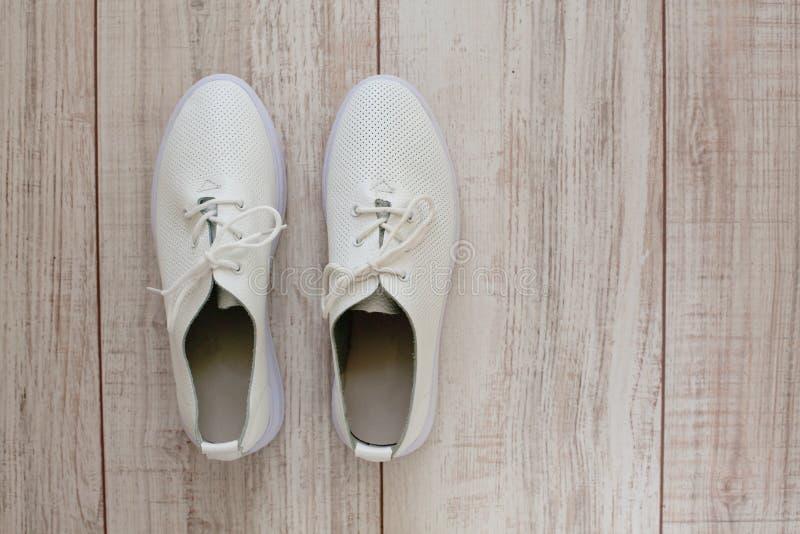 Sapatilhas de couro brancas no fundo de madeira fotos de stock royalty free
