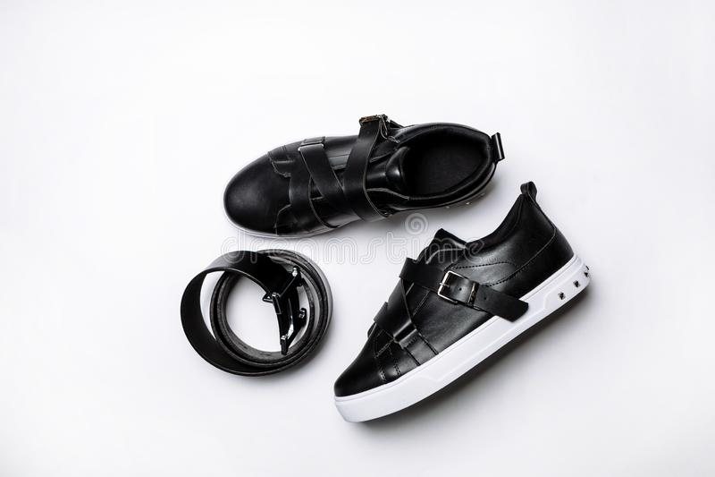 Sapatilhas de couro pretas com correias e ?nico e cintur?o negro de couro branco em um fundo branco foto de stock royalty free