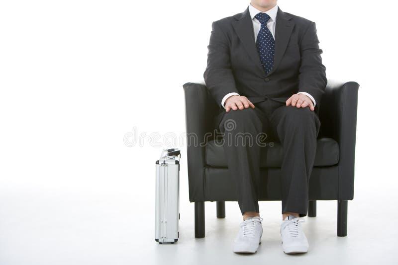 Sapatilhas desgastando de assento do homem de negócios fotos de stock