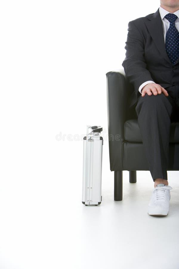 Sapatilhas desgastando de assento do homem de negócios imagem de stock royalty free