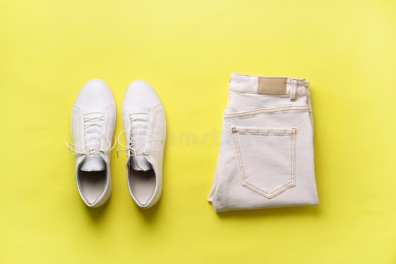 Sapatilhas e calças de brim brancas fêmeas no fundo amarelo com espaço da cópia Vista superior Forma do verão, compra, cápsula foto de stock