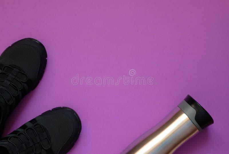 Sapatilhas e garrafa pretas do metal no espaço violeta da cópia do whith do fundo foto de stock