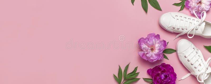 Sapatilhas fêmeas brancas da forma e peônias roxas cor-de-rosa das flores no fundo cor-de-rosa Configura??o lisa, vista superior, fotografia de stock