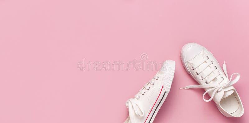 Sapatilhas fêmeas brancas da forma no fundo cor-de-rosa Configura??o lisa, vista superior, espa?o da c?pia Sapatas do `s das mulh imagens de stock