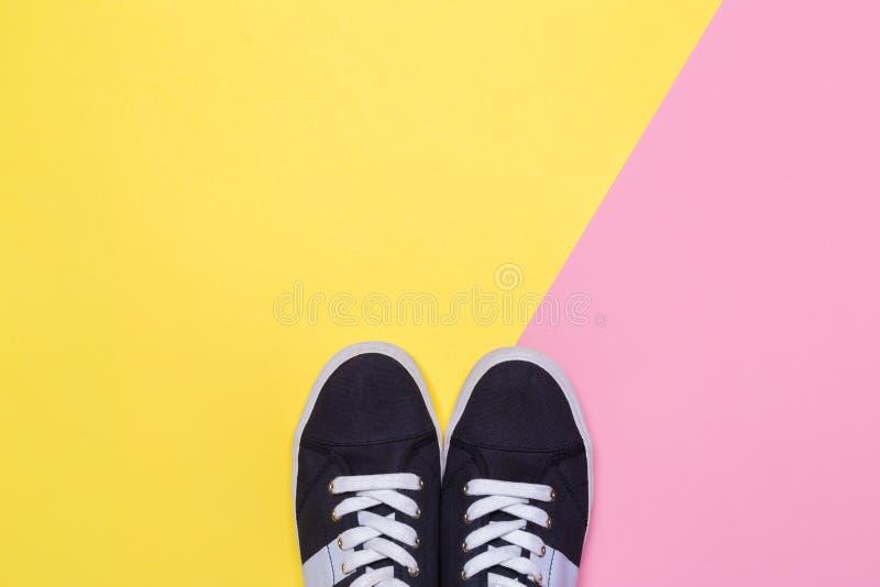 Sapatilhas no rosa e no fundo amarelo Conceito do blogue ou do compartimento da forma fotografia de stock royalty free