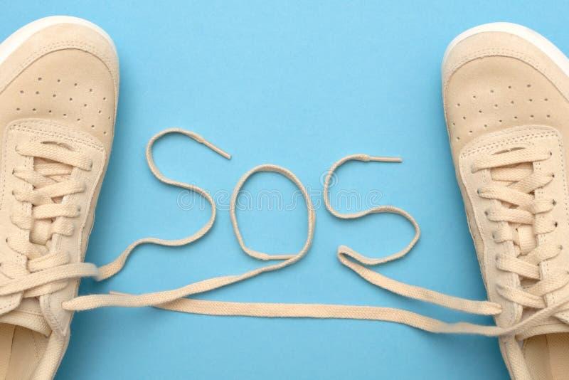 Sapatilhas novas das mulheres com laços no texto do SOS Excepto nossas almas imagens de stock