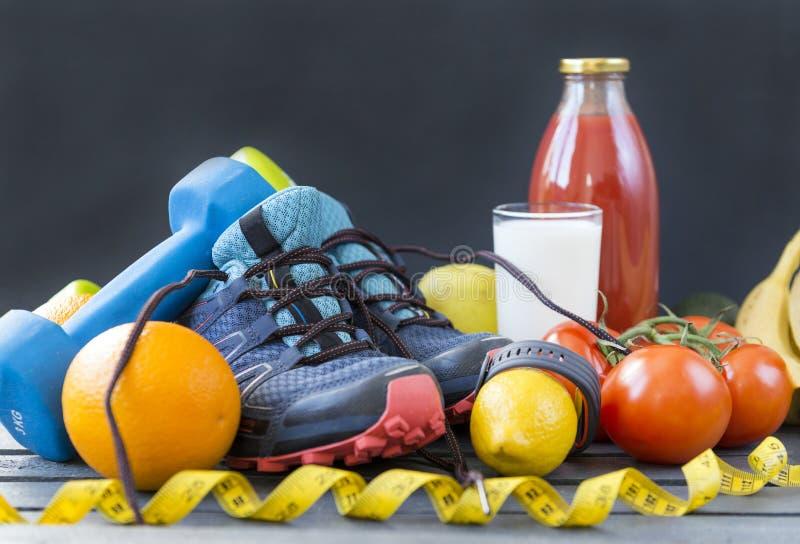 sapatilhas, pesos, laranjas, tomates, limão, esportes bracelete, suco de tomate, leite, frutas e legumes imagens de stock
