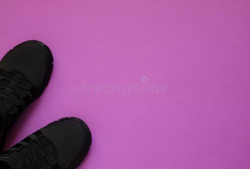 Sapatilhas pretas no espaço violeta da cópia do whith do fundo imagens de stock