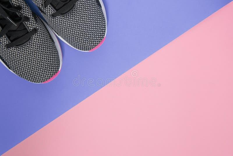 Sapatilhas preto e branco com a sola cor-de-rosa no fundo ultravioleta e cor-de-rosa Conceito do treinamento lifestile e diário s imagens de stock