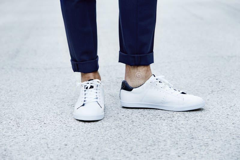 Sapatilhas vestindo do homem foto de stock