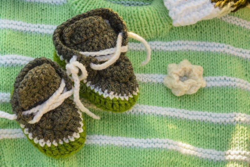 Sapatinhos de lã feitos a mão do bebê foto de stock