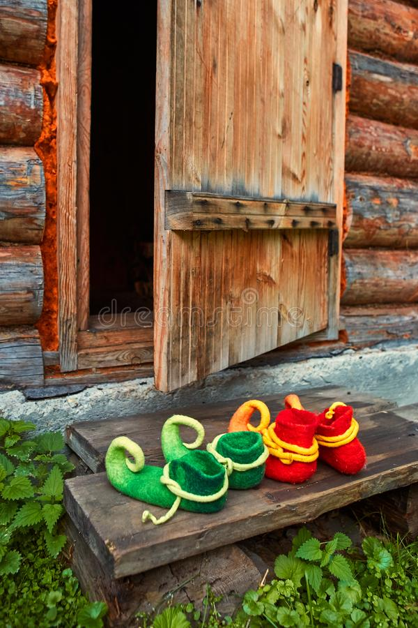Sapatos criaturas fabulosas no limiar de uma casa de madeira perto da porta aberta fotografia de stock