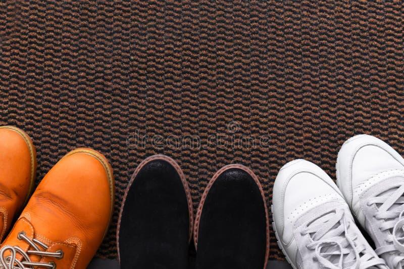 Sapatos de homens e mulheres diferentes, par de tênis num tapete de sapato, vista superior fotografia de stock