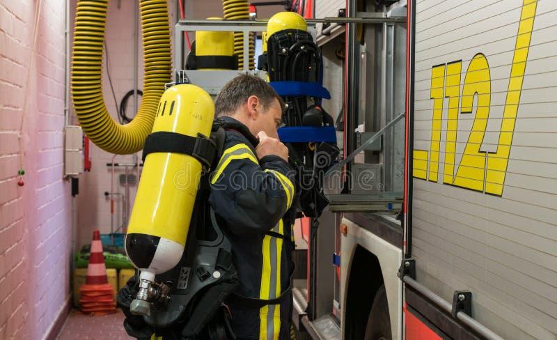 Sapeur-pompier avec le cylindre d'oxygène sur le camion de pompiers images libres de droits