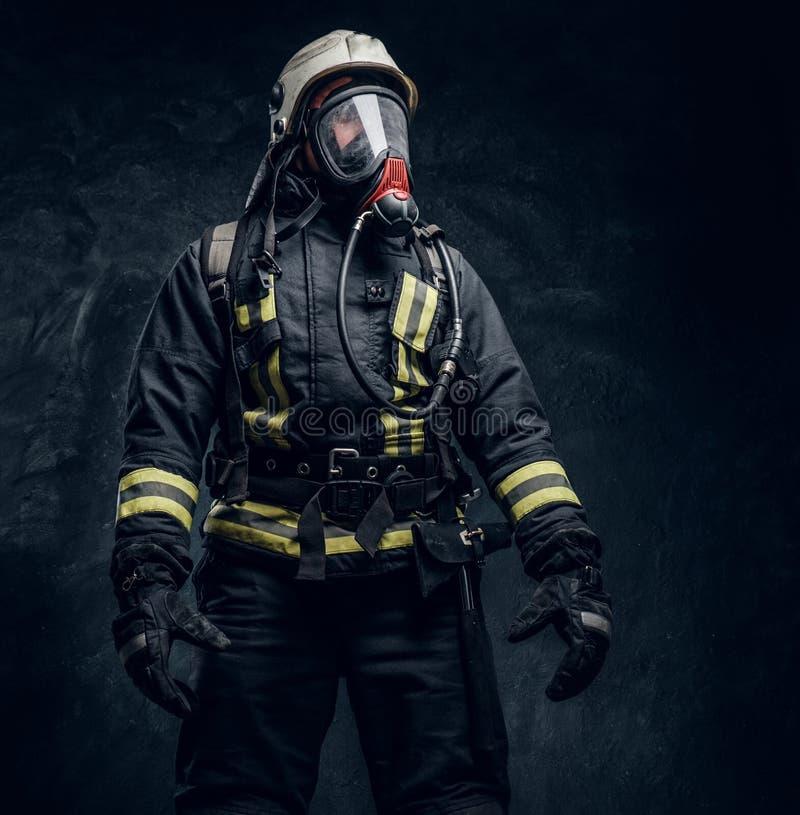 Sapeur-pompier dans le casque de sécurité et masque à oxygène portant les vêtements protecteurs images stock