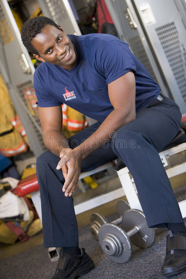 Sapeur-pompier dans le vestiaire de caserne de pompiers photos stock