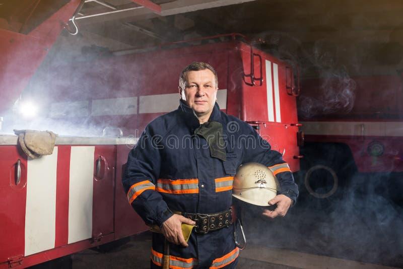 Sapeur-pompier de pompier dans l'action se tenant près d'un firetruck photographie stock libre de droits