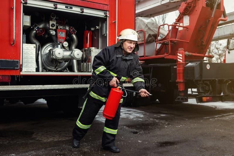 Sapeur-pompier de pompier dans l'action se tenant près d'un firetruck EMER photographie stock libre de droits