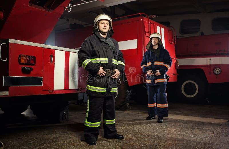 Sapeur-pompier de pompier dans l'action se tenant près d'un firetruck EMER photographie stock